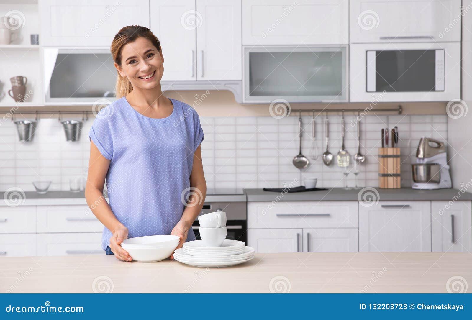 Mulher com os pratos limpos perto da tabela na cozinha