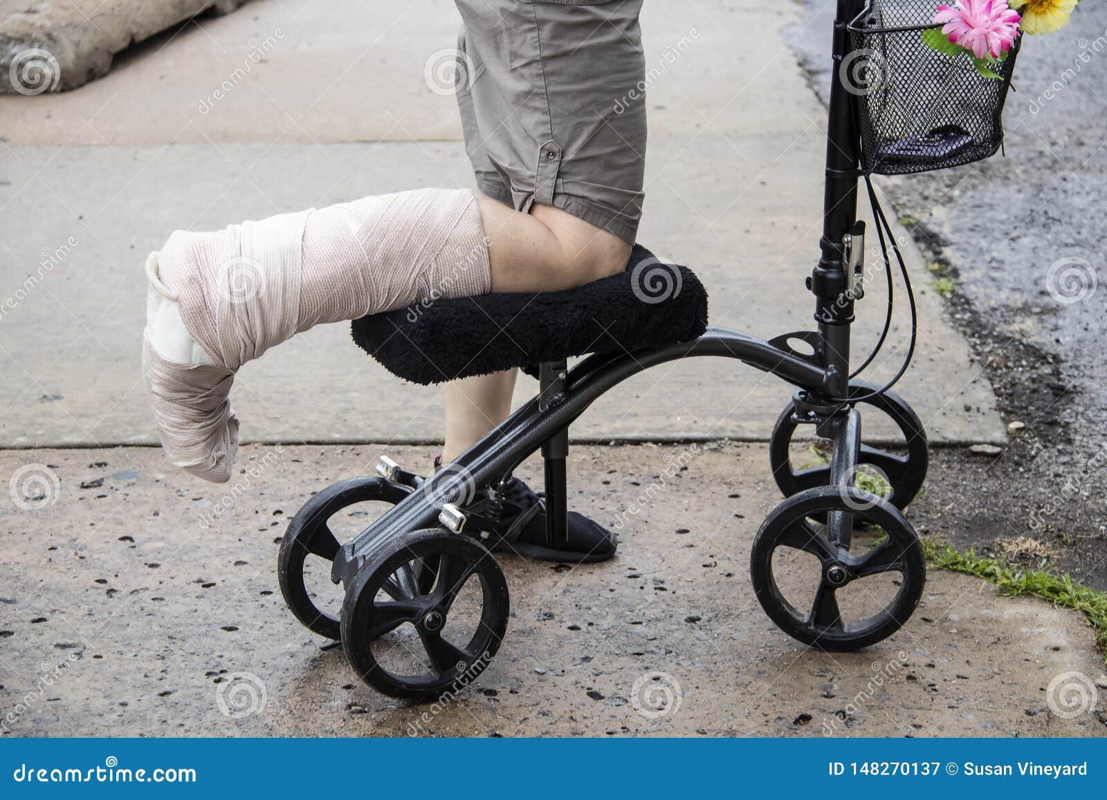 Mulher com pé envolvido no  trotinette  steerable do caminhante do joelho com as flores na cesta e o telefone celular para dentro