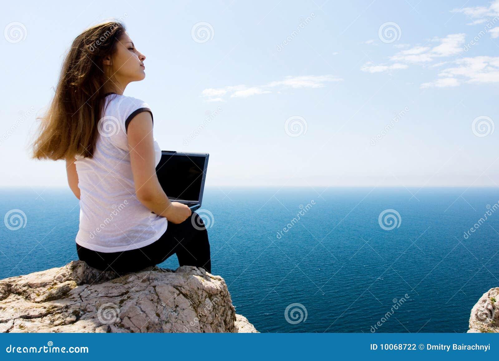 Mulher com portátil e mar
