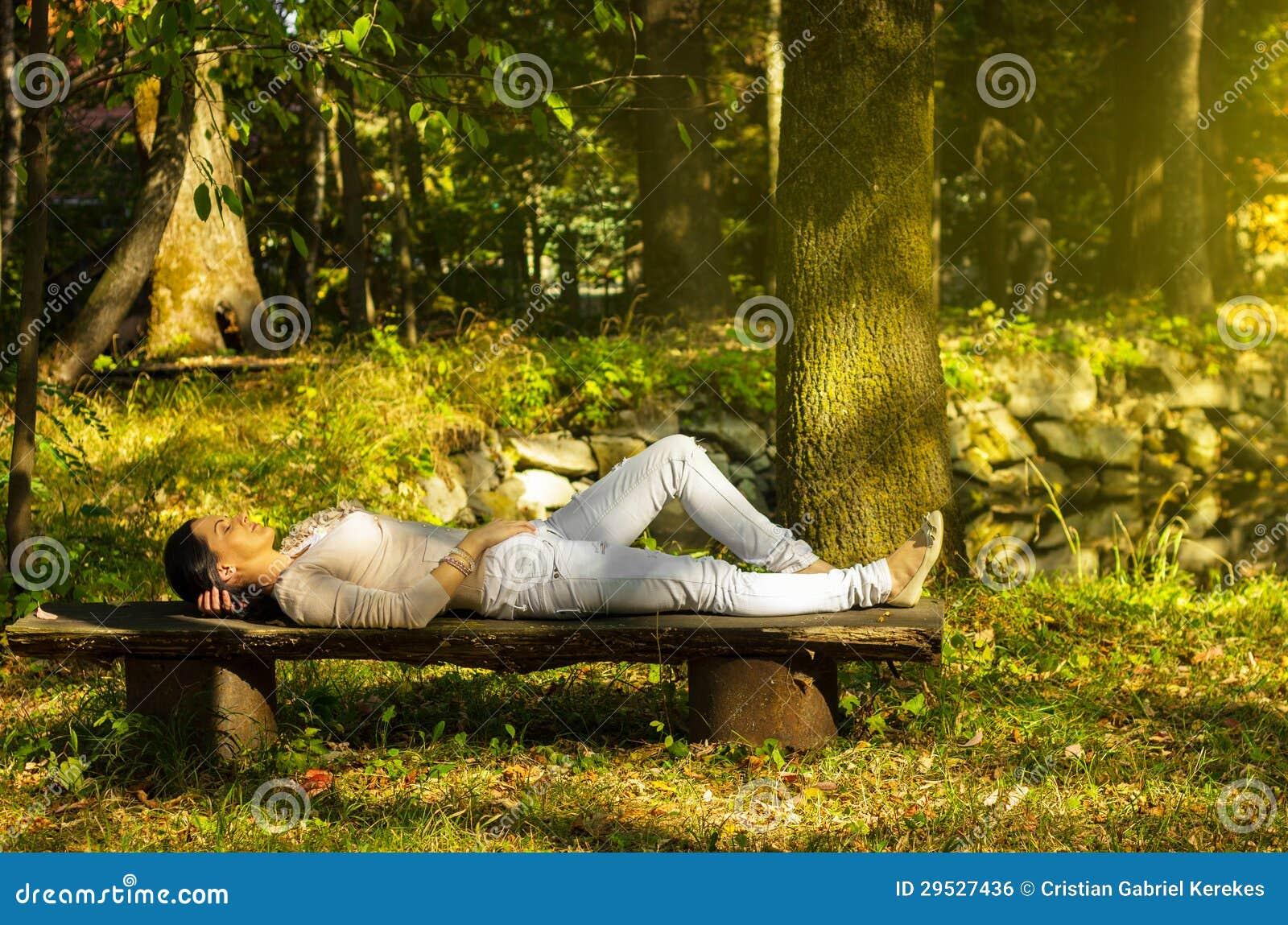 Mulher com relaxamento fechado dos olhos em um banco na natureza