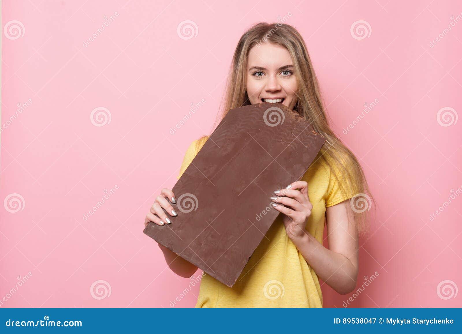Mulher com sorriso do chocolate Menina bonito que guarda e que come a barra de chocolate gigante do cacau perto da parede cor-de-