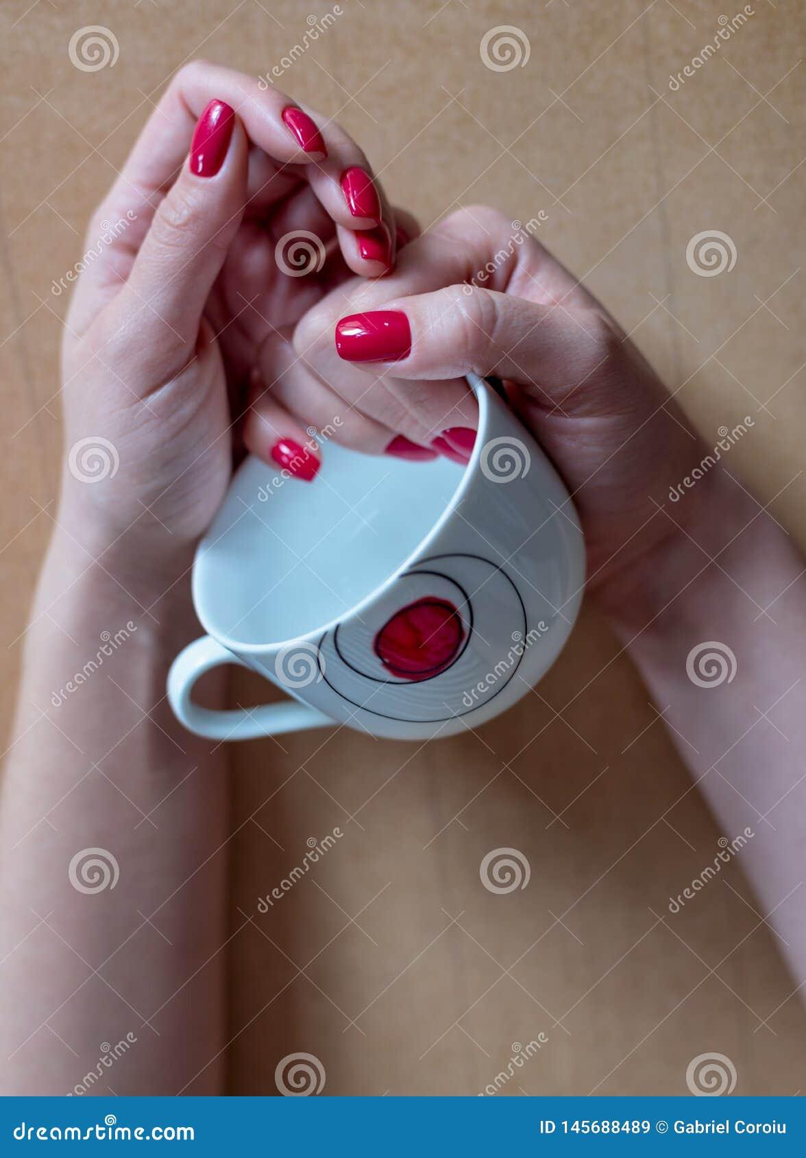 A mulher com tratamento de mãos vermelho guarda um copo de café vazio nela
