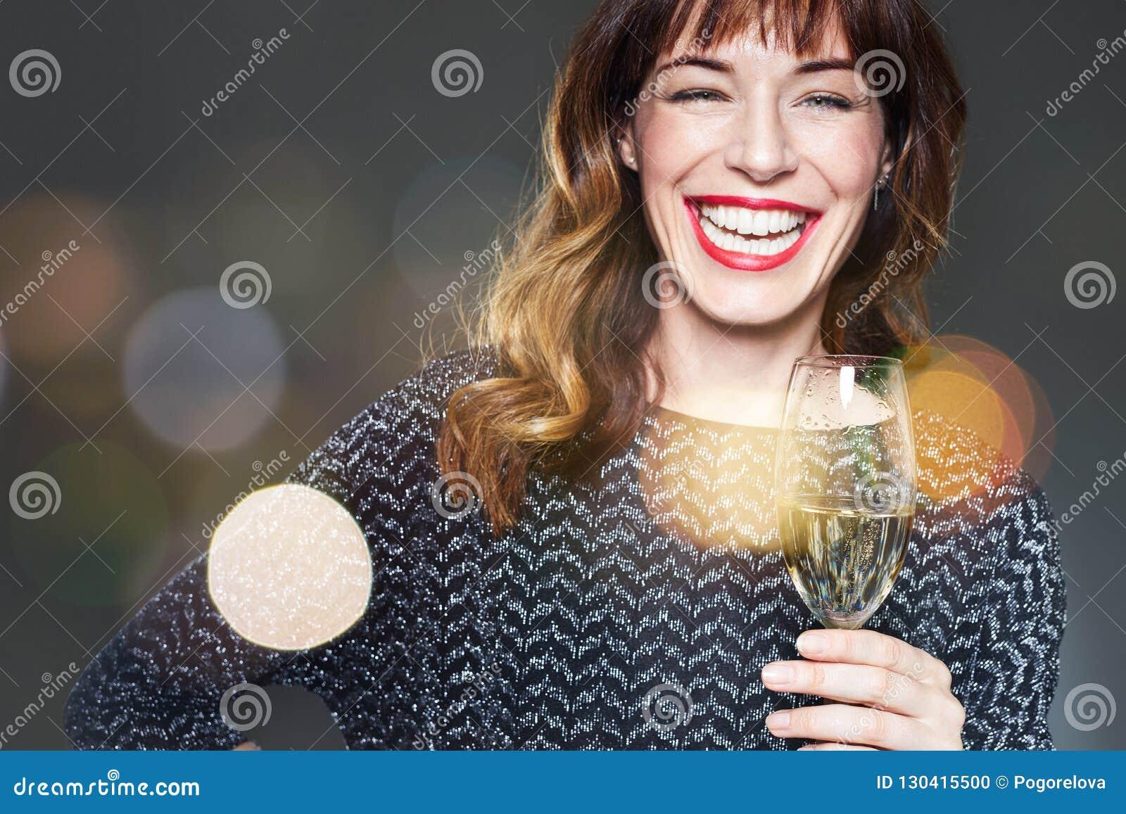 Mulher com um vidro do champanhe no fundo, em alargamentos e no bokeh escuros Senhora com comemoração longa e laughi dos bordos d
