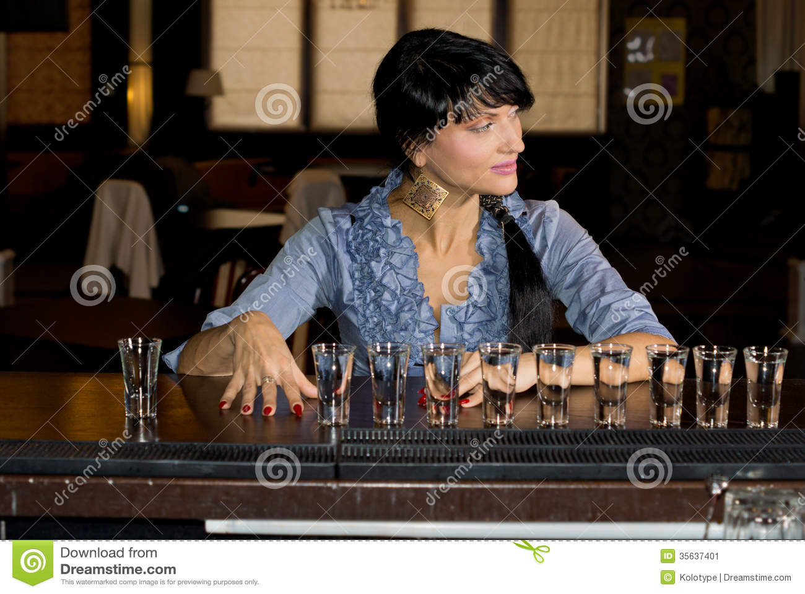 Mulher com uma fileira de vidros de tiro da vodca