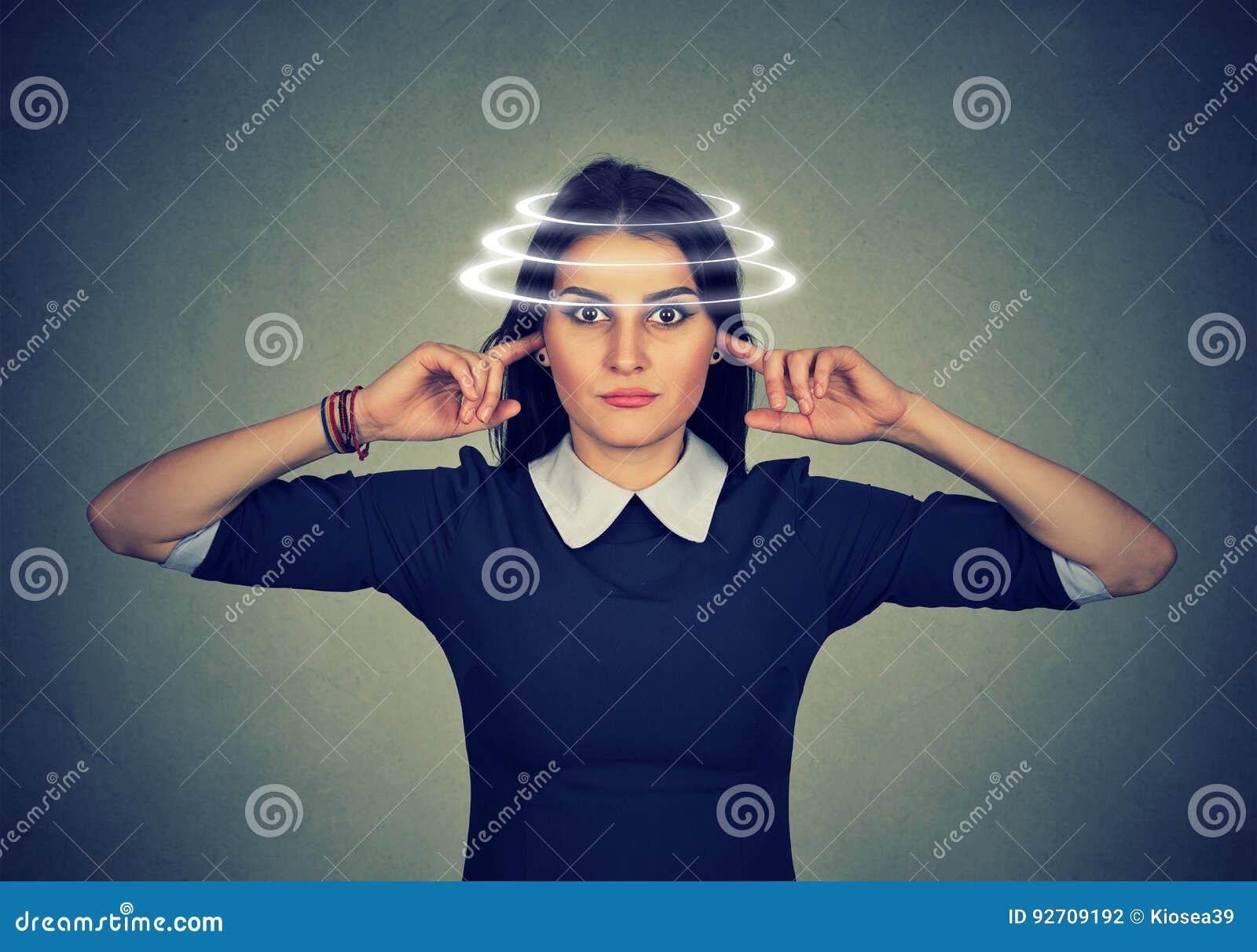 Mulher com a vertigem que fecha suas orelhas do ruído