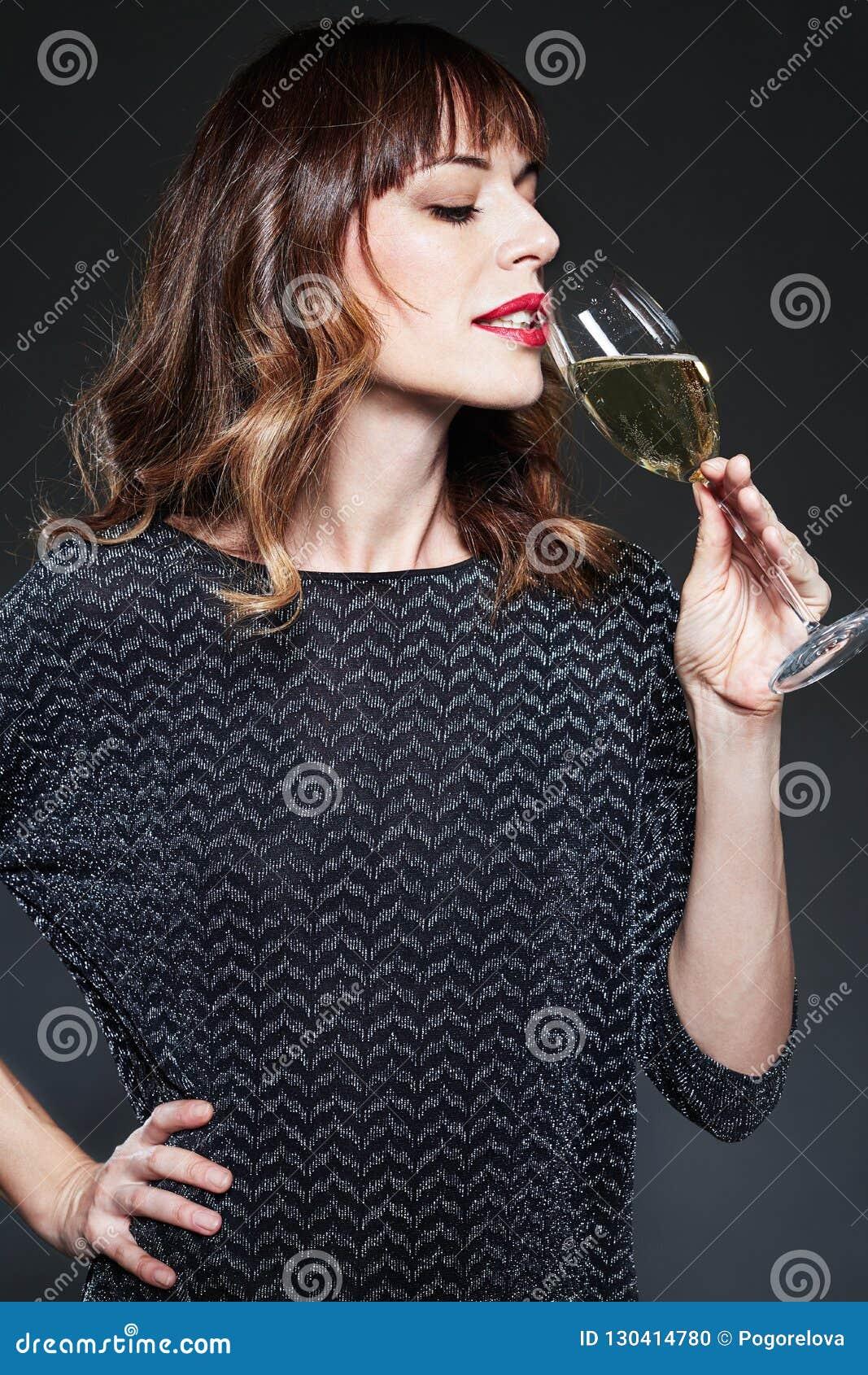Mulher com vidro do vinho espumante bebendo do champanhe no fundo escuro Senhora com cabelo encaracolado longo que comemora Retra