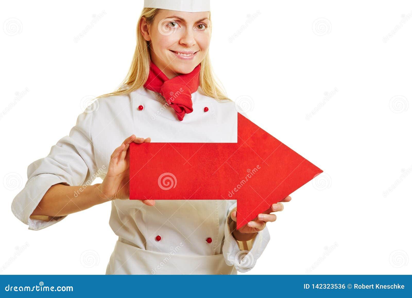 A mulher como um cozinheiro está guardando a seta