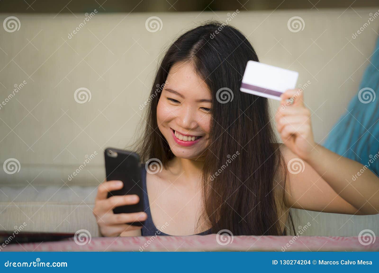Mulher coreana asiática feliz e bonita nova que guarda o cartão de crédito usando o telefone celular para Internet banking e o sm