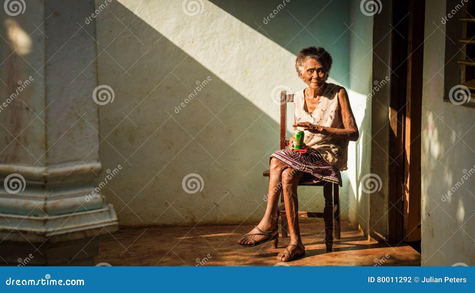 Mulher cubana idosa na cadeira que aprecia uma cerveja