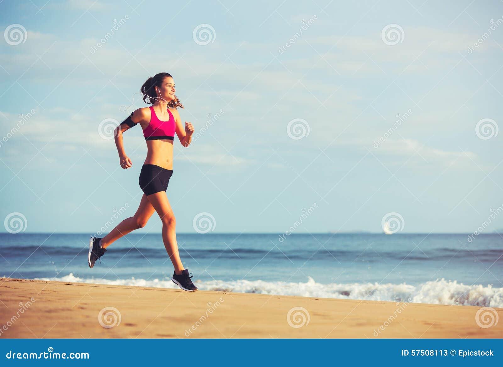 Mulher da aptidão dos esportes que corre na praia no por do sol