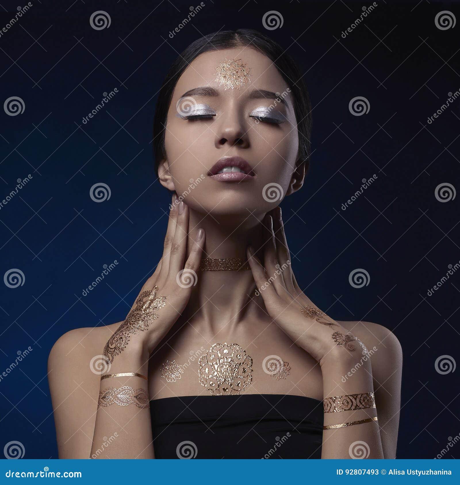 Mulher da beleza com teste padrão dourado de Mehendi