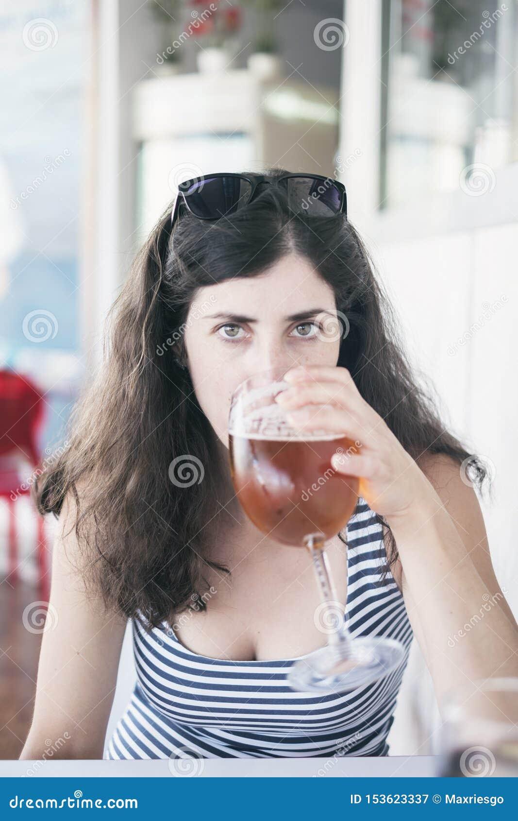 Mulher da beleza que bebe um copo da cerveja no restaurante