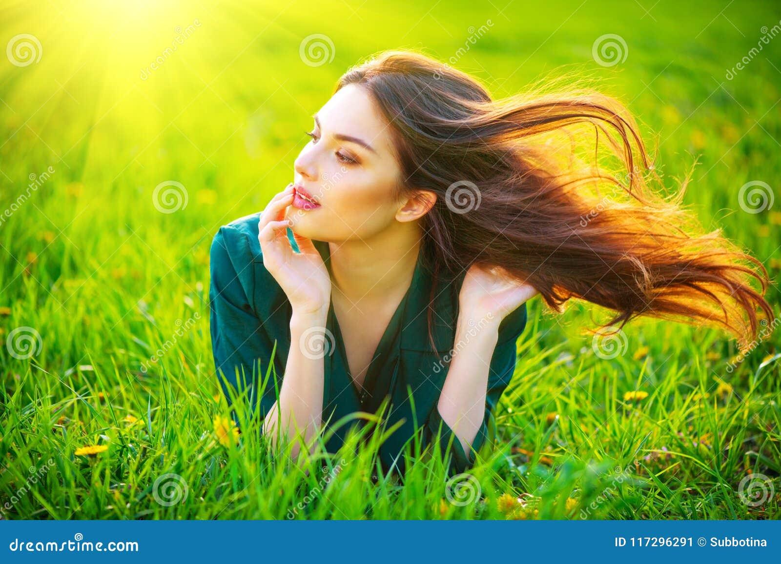 Mulher da beleza que encontra-se no campo que aprecia a natureza Menina moreno bonita com cabelo longo saudável do voo
