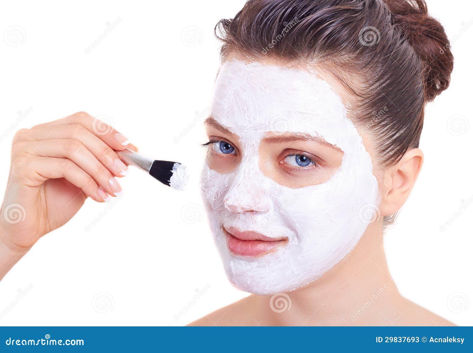 Mulher da beleza que obtem a máscara facial isolada