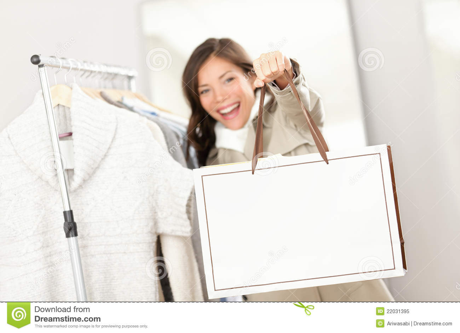 f1f32d544 Mulher da compra que mostra o sinal do saco de compra com espaço da cópia.  Cliente que procura a roupa dentro na loja de roupa.