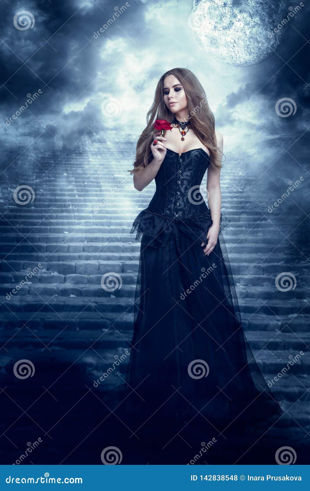 Mulher da fantasia no vestido preto que cheira Rose Flower, menina místico no vestido gótico retro longo
