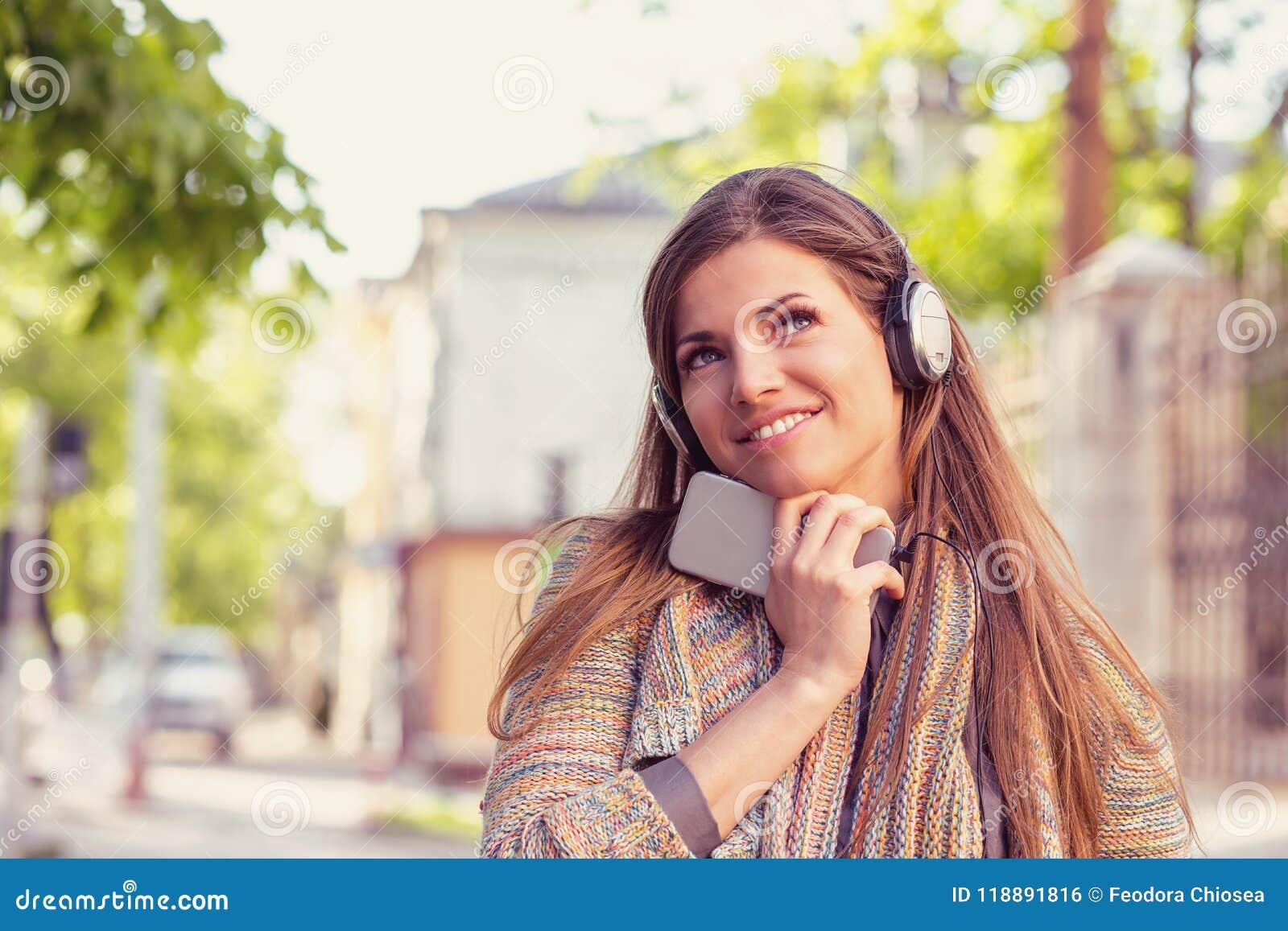 Mulher da fantasia que escuta a música em um telefone esperto que anda abaixo da rua em um dia ensolarado do outono