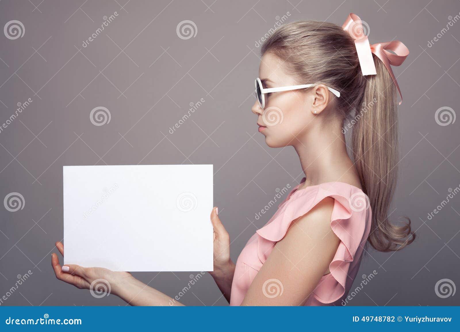 Mulher da forma nos óculos de sol com placa de papel vazia nas mãos