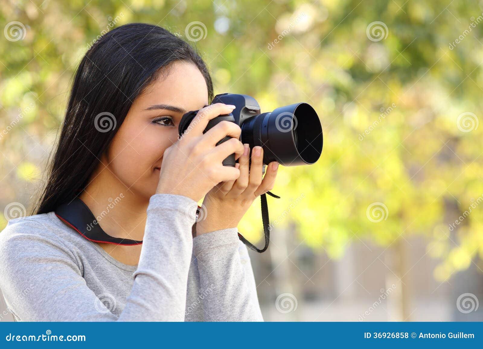 Mulher da fotografia que aprende a fotografia em um parque