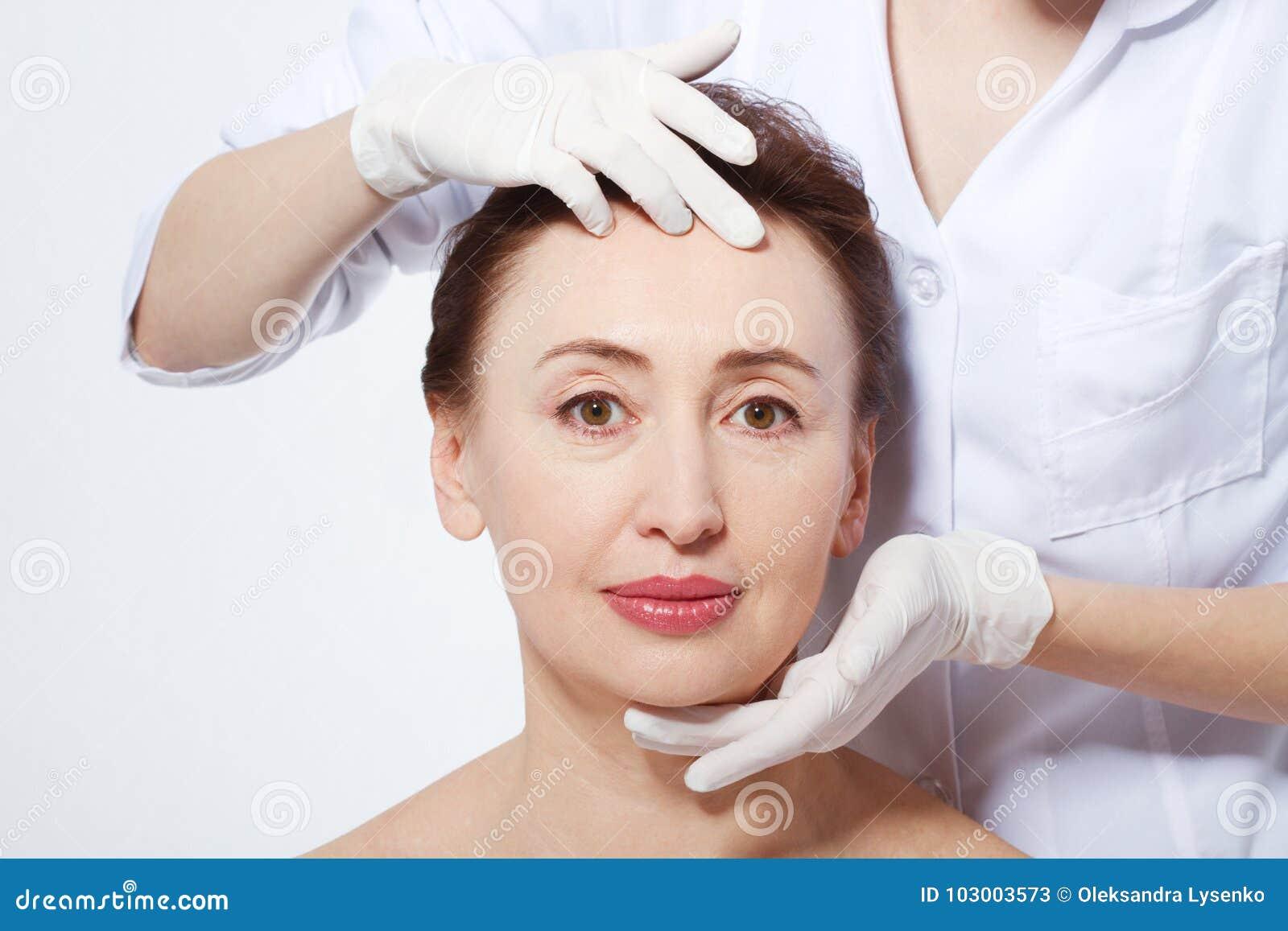 Mulher da Idade Média que obtém o tratamento dos termas Massagem de cara Botox e colagênio antienvelhecimento O conceito da cirur