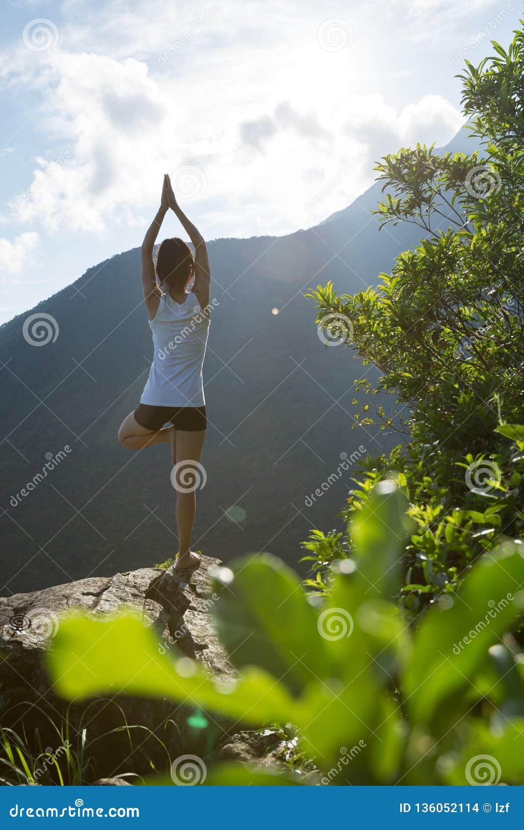 Mulher da ioga que medita sobre a borda do penhasco do pico de montanha