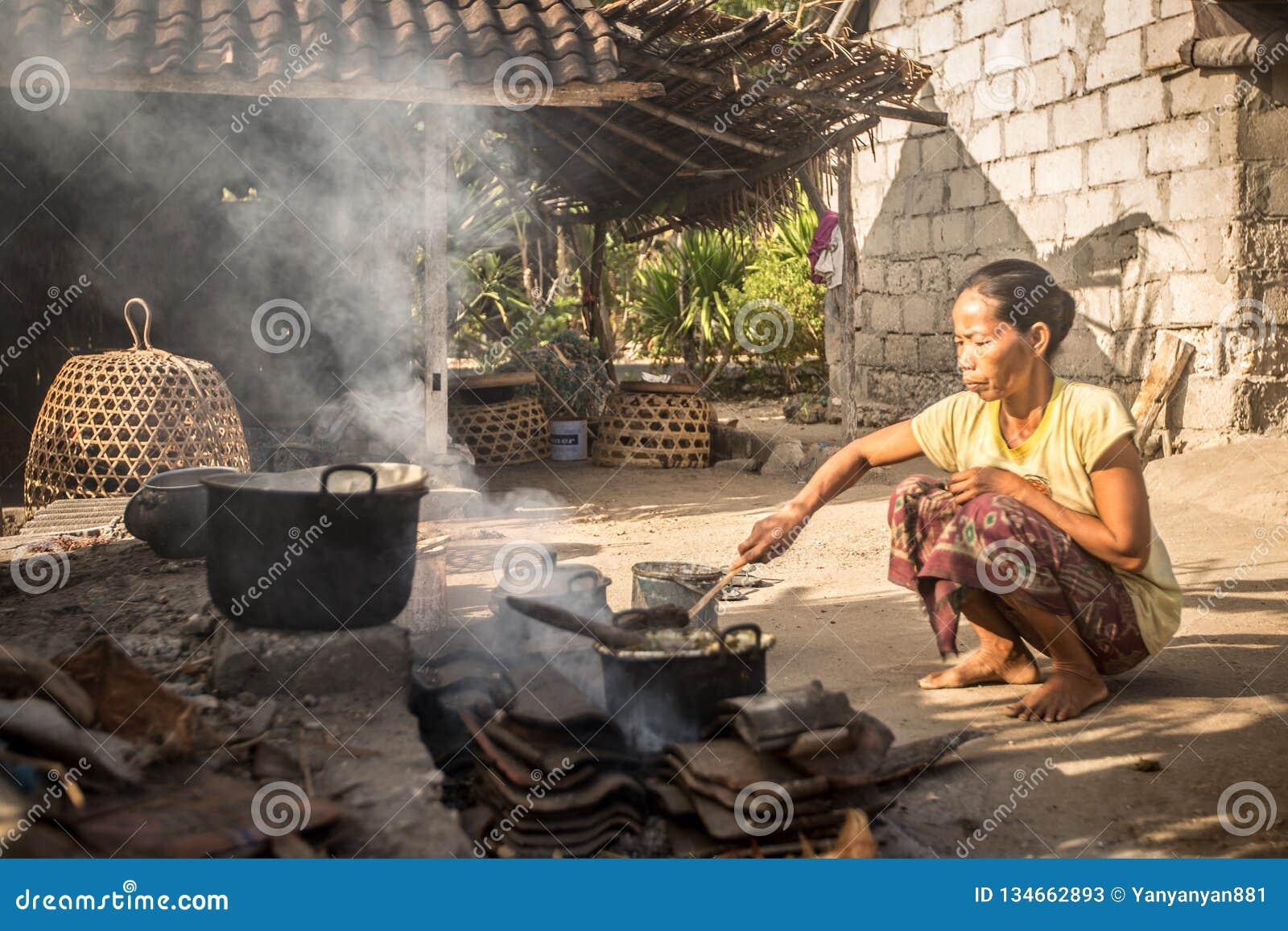 A mulher da pobreza cozinha a refeição usando fundamentos básicos