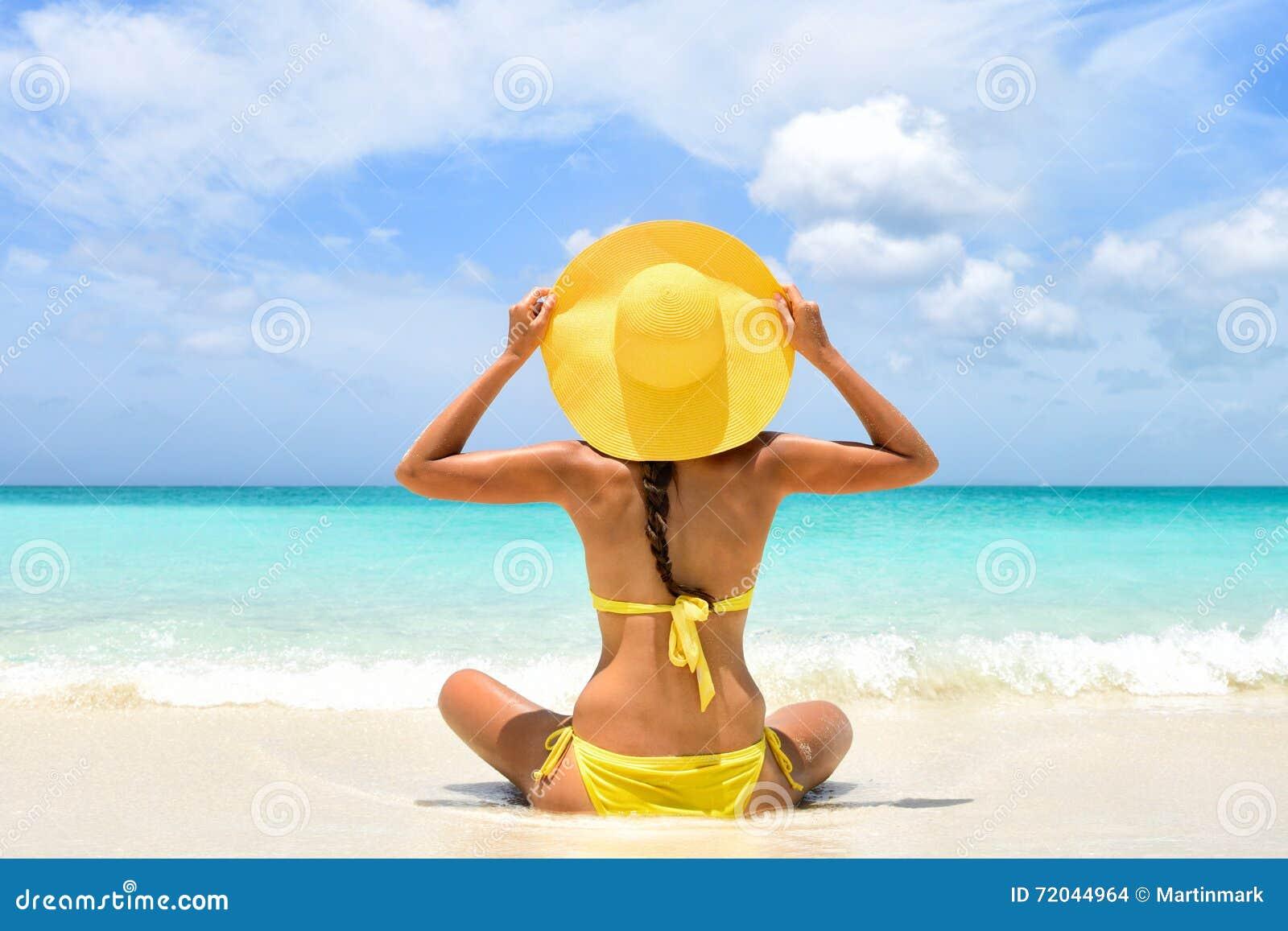 Mulher das férias da praia do verão que aprecia o feriado do sol