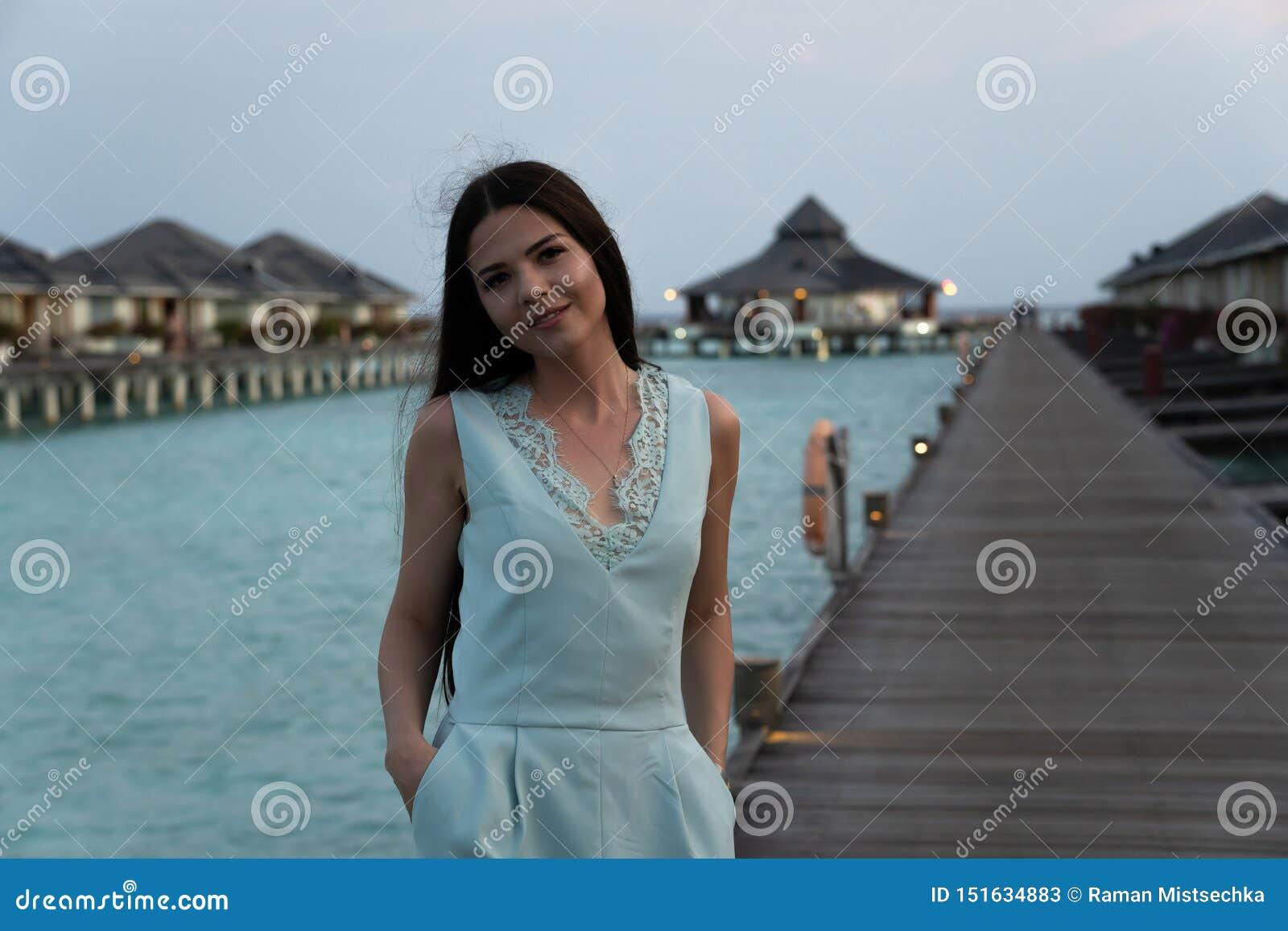 Mulher das férias da praia que anda na ponte sobre o hotel de luxo dos bungalows no fundo