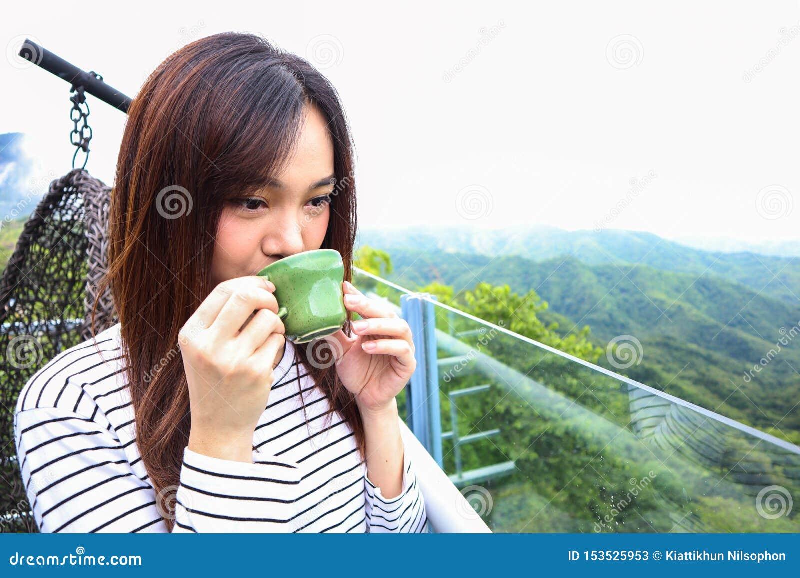 Mulher de Ásia que aprecia a manhã sereno bonita que olha o céu do cenário da paisagem da natureza das montanhas que começa o caf