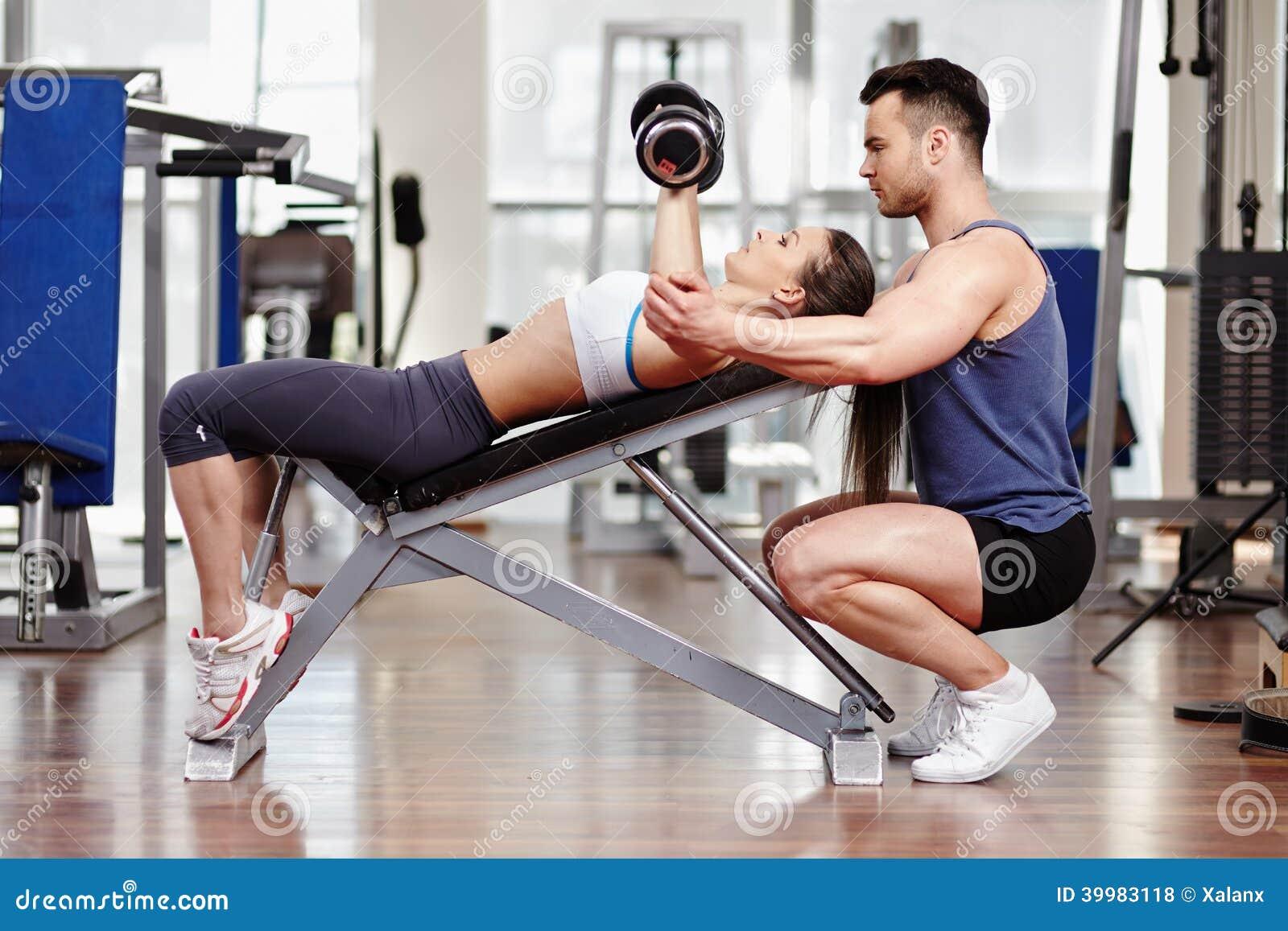 Mulher de ajuda do instrutor pessoal no gym