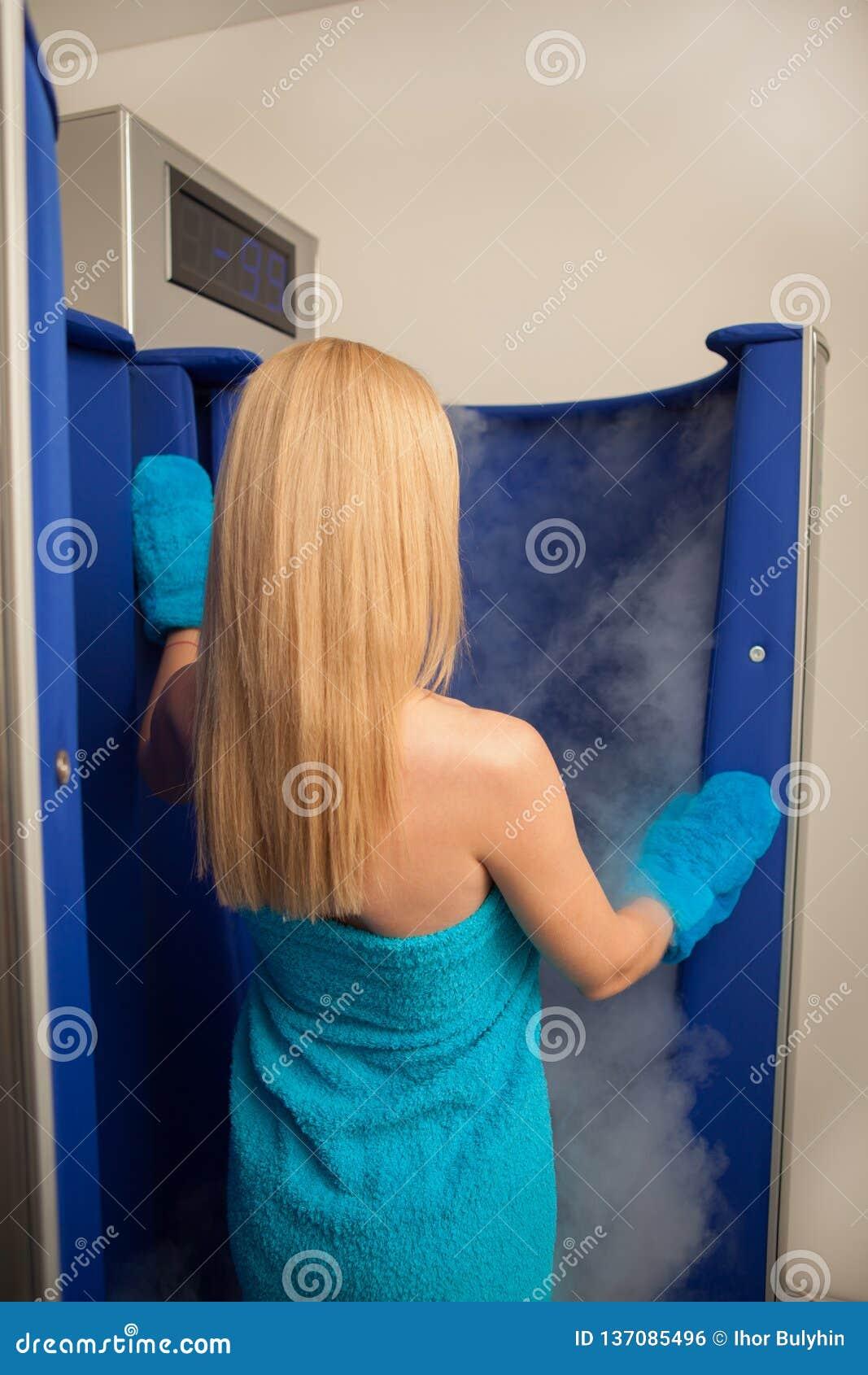 Mulher de cabelo loura que entra na cabine cryotherapy da sauna
