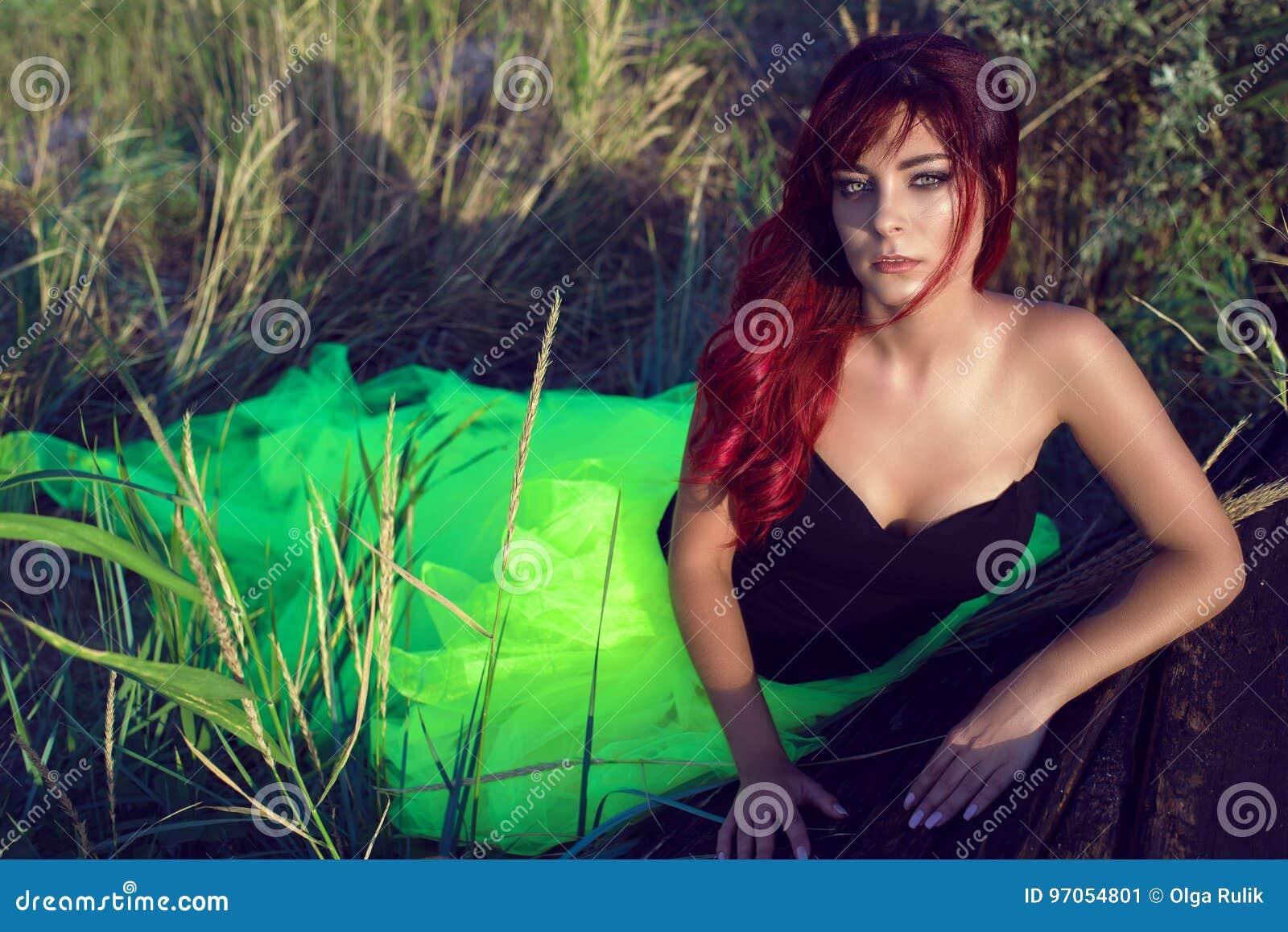 A mulher de cabelo vermelha bonita no encobrimento verde do espartilho preto e da cauda longa contorna a inclinação no barco de m