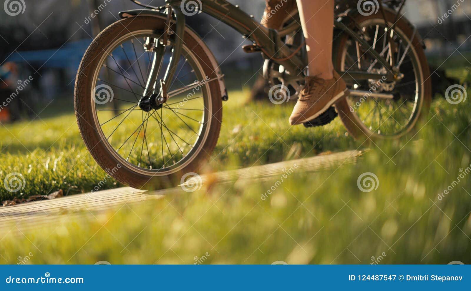 Mulher de cabelo vermelha que senta-se na bicicleta que encontra-se na grama no parque da cidade Parque da bicicleta da mulher