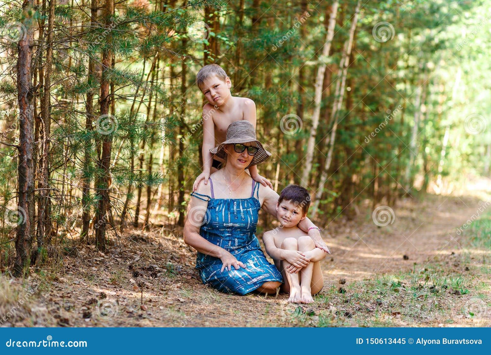Mulher de cinquenta anos e dois rapazes pequenos na floresta do verão