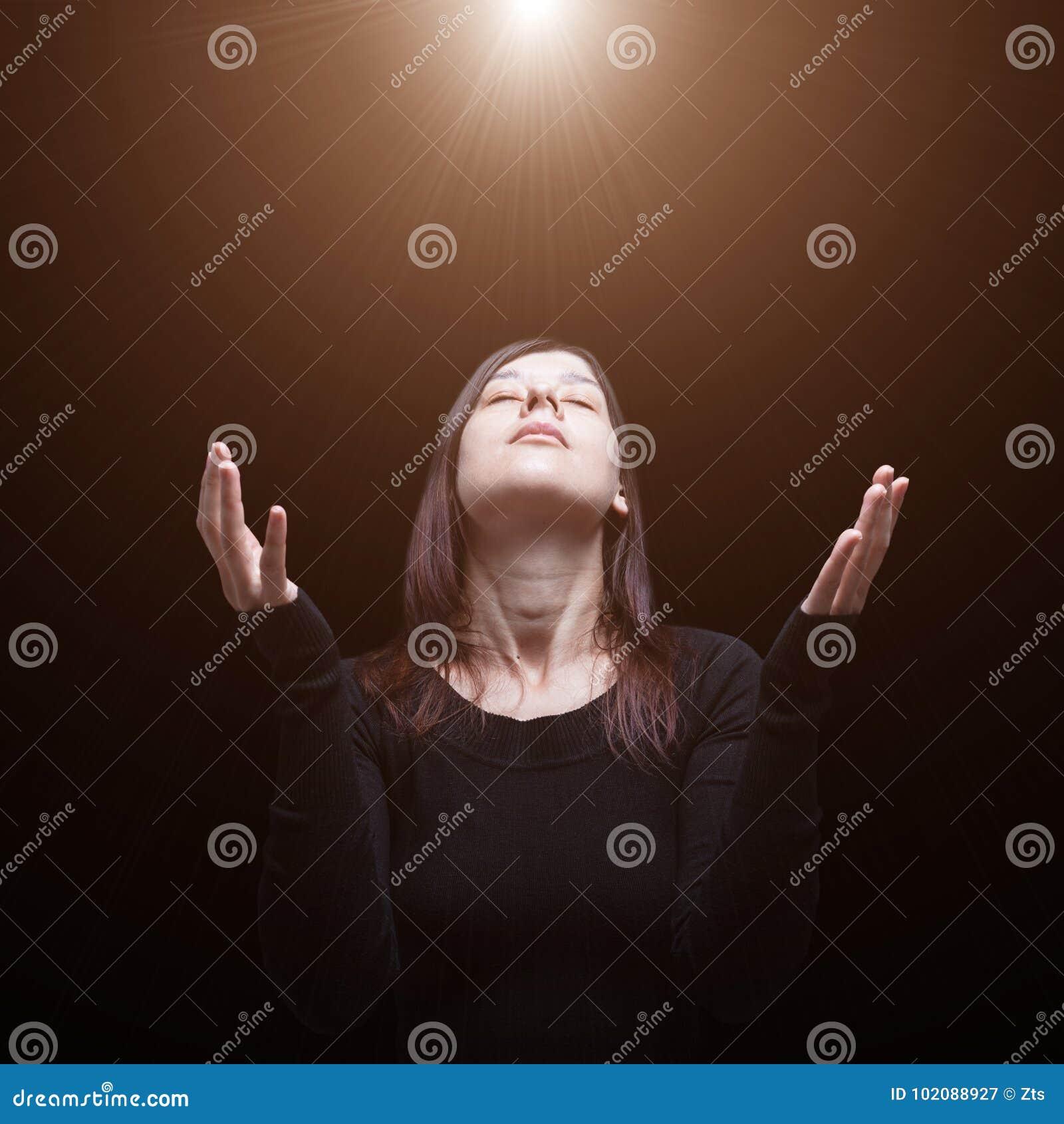 Mulher de lamentação que reza, com os braços estendido na adoração ao deus