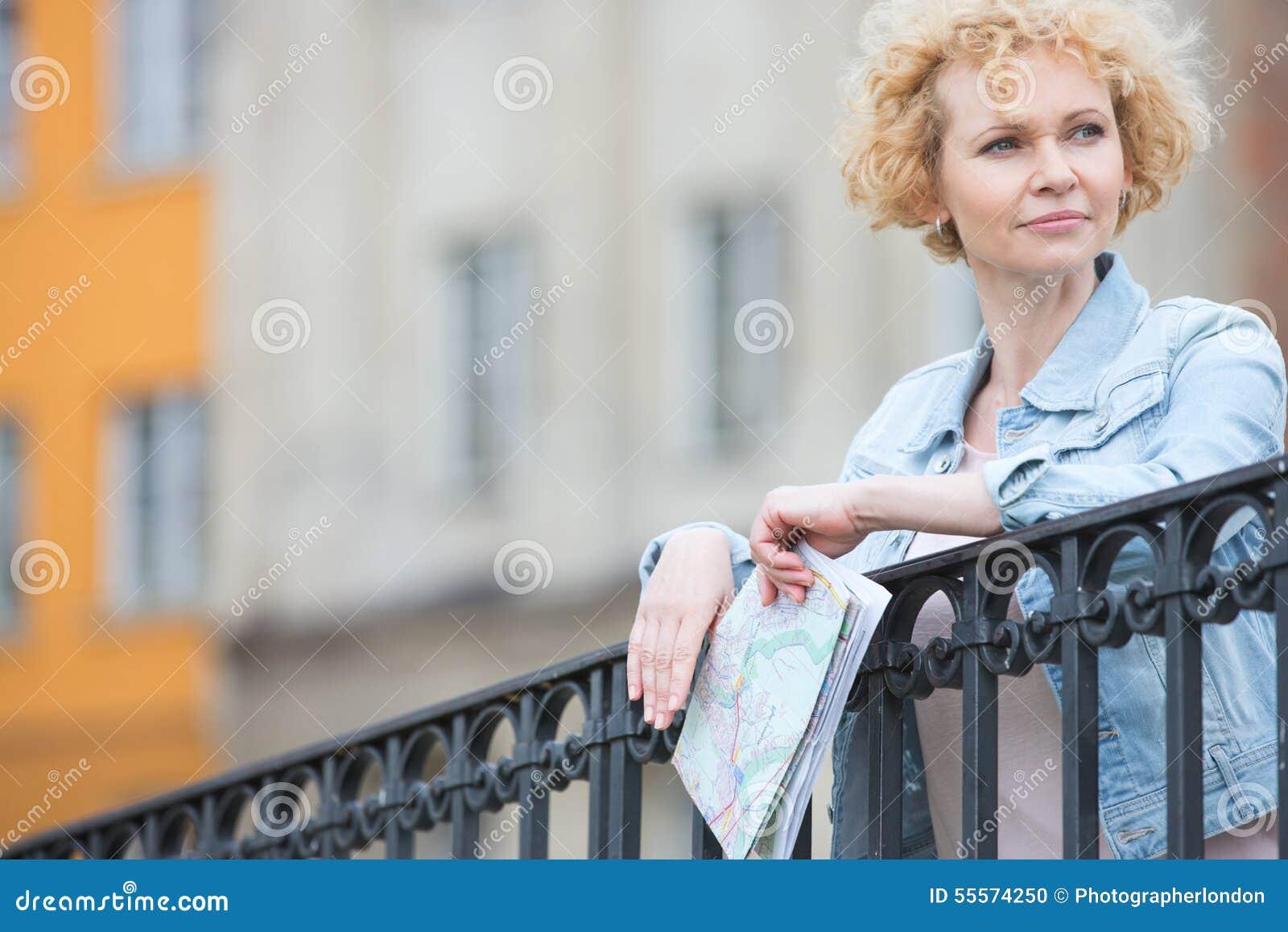 Mulher de meia idade pensativa que guarda o mapa ao inclinar-se no cerco