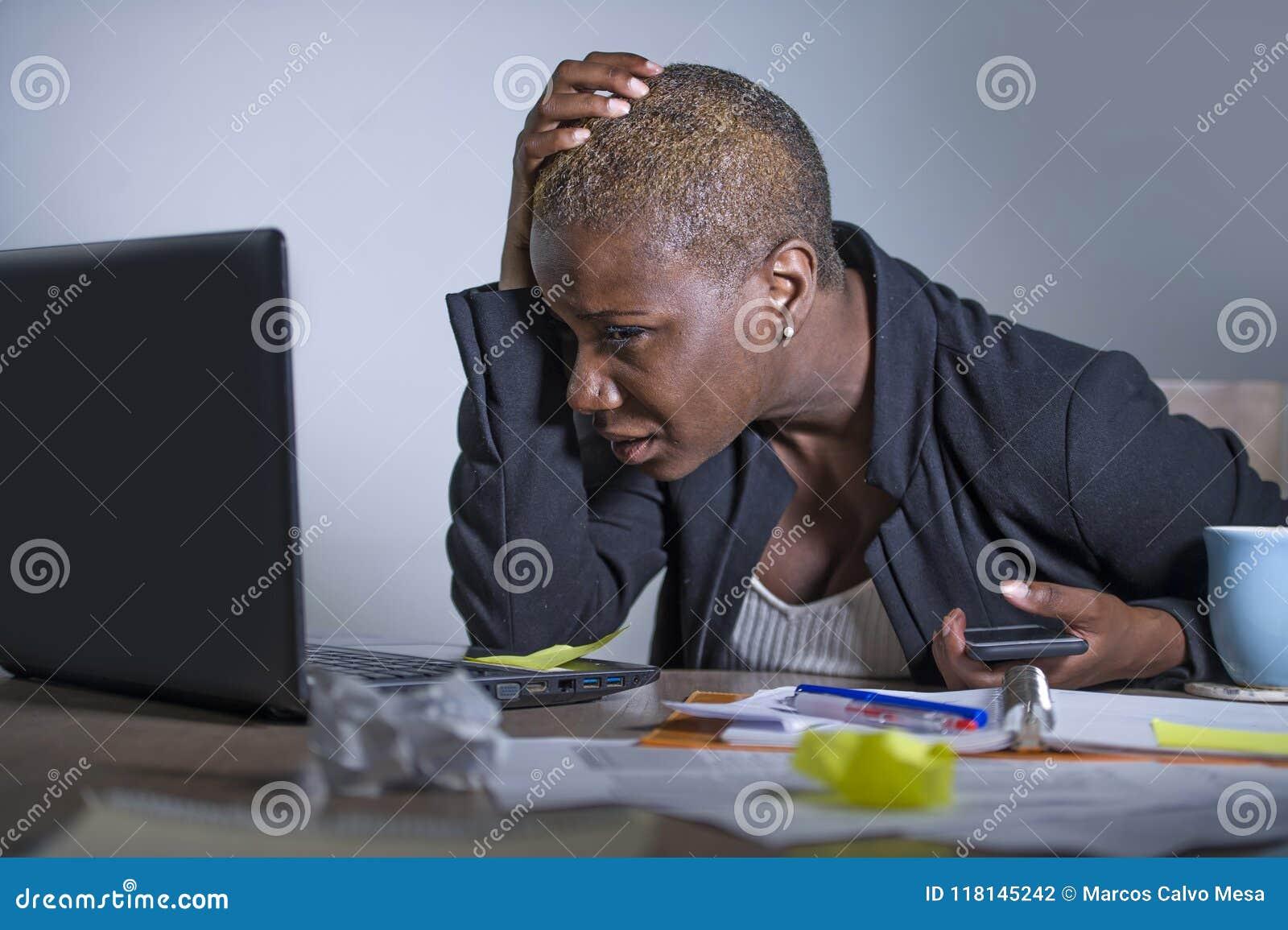 Mulher de negócio afro-americano desesperada e forçada nova que trabalha na mesa do laptop no esforço do sofrimento do escritório