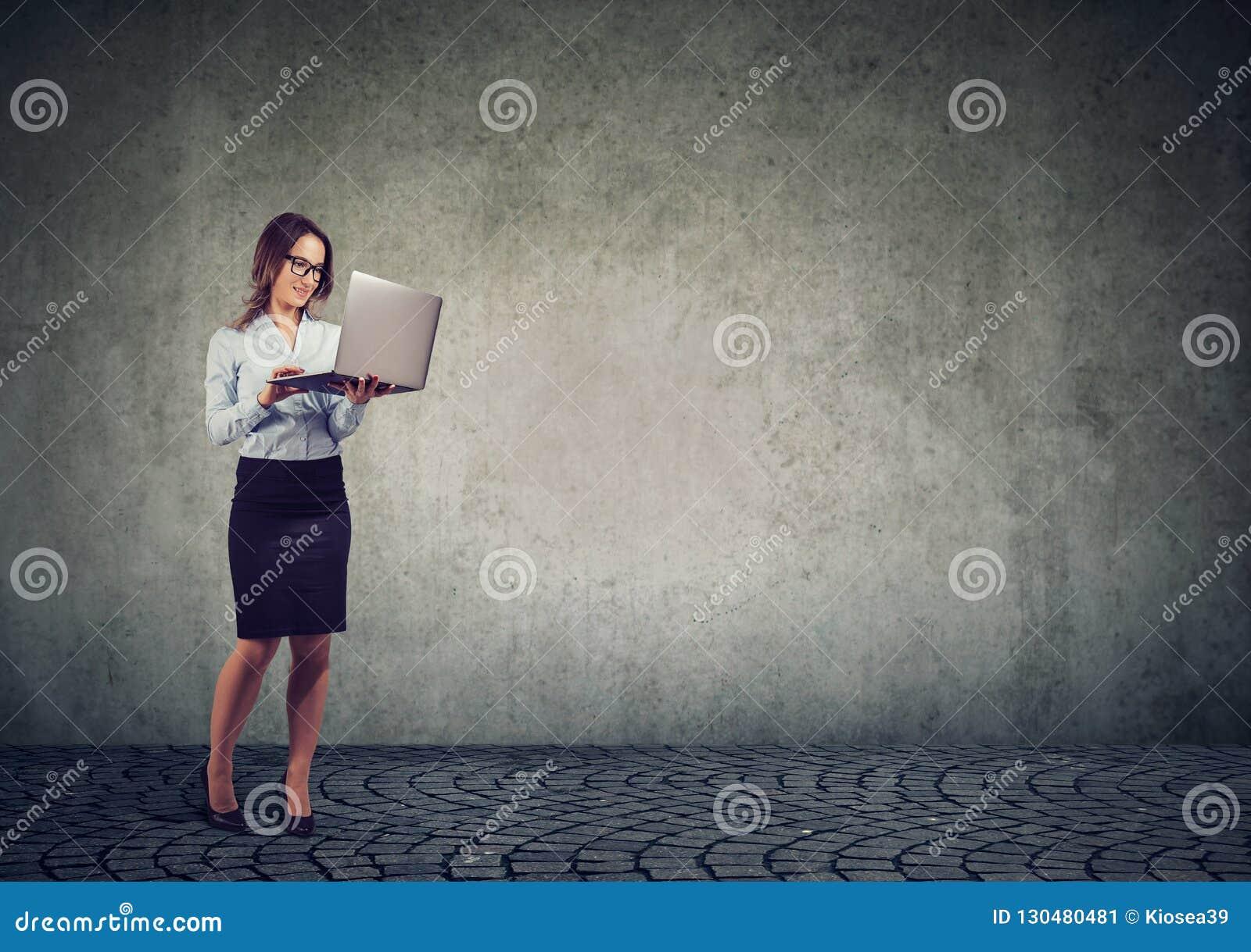 Mulher de negócio alegre que usa o portátil
