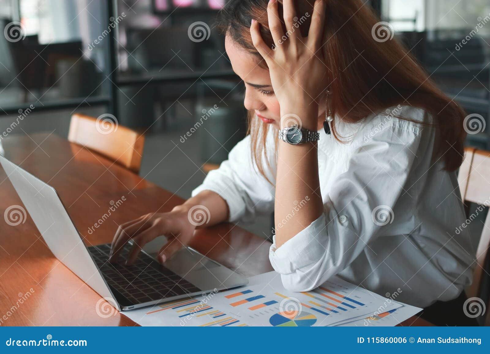 Mulher de negócio asiática nova frustrante deprimida com o portátil que sofre de fatigante no escritório