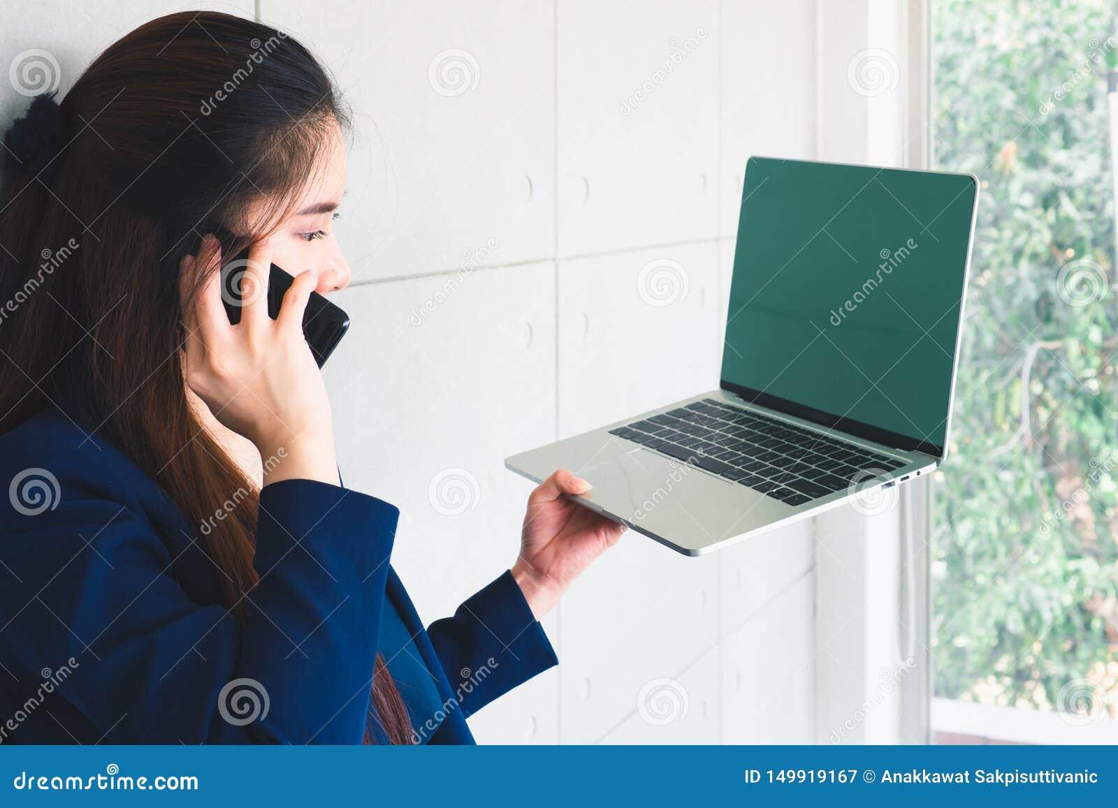 Mulher de negócio bonita asiática que fala e que olha dados no portátil