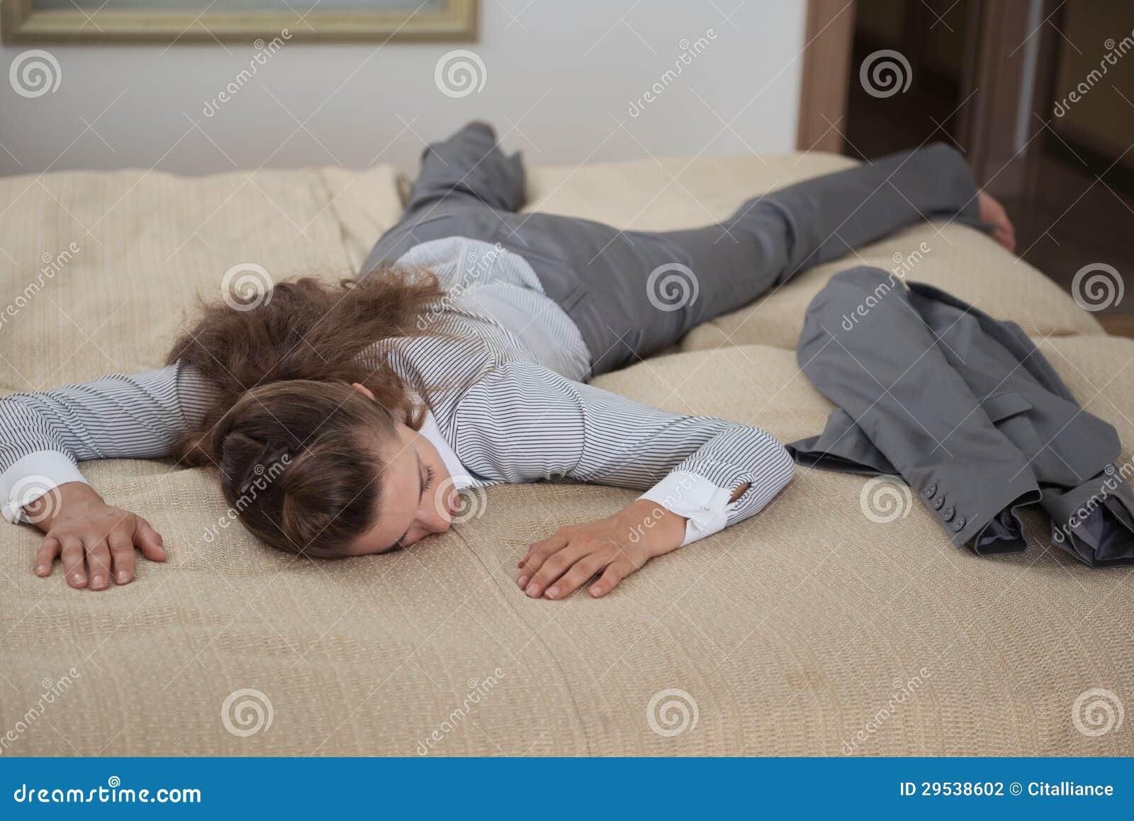 A mulher de negócio cai para baixo da exaustão na sala