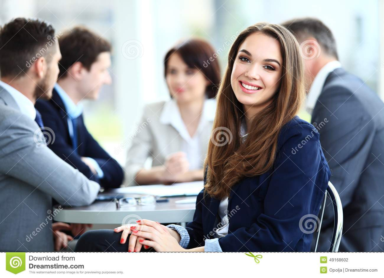 Mulher de negócio com seu pessoal, grupo dos povos no fundo