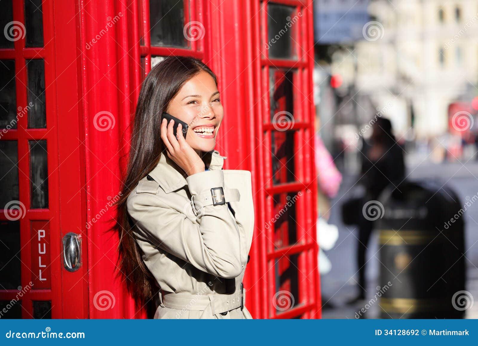 Mulher de negócio de Londres no telefone esperto pela cabine vermelha