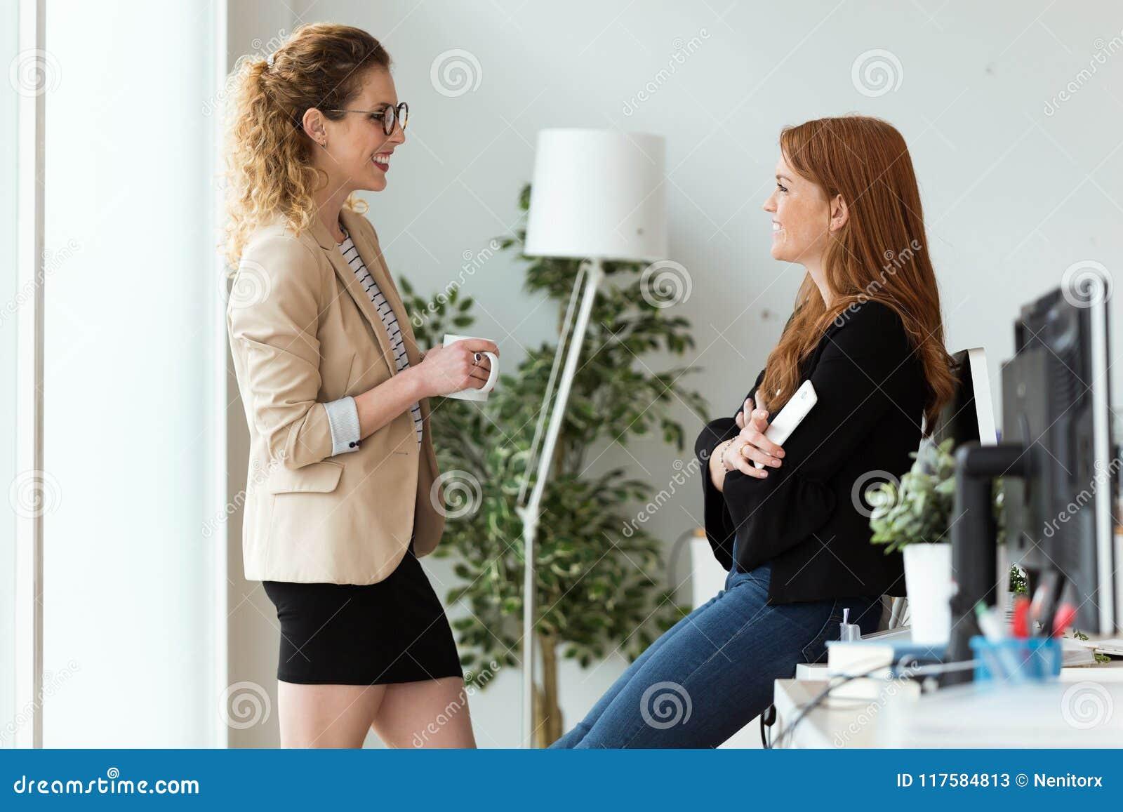 Mulher de negócio dois consideravelmente nova que relaxa um momento ao beber o café no escritório