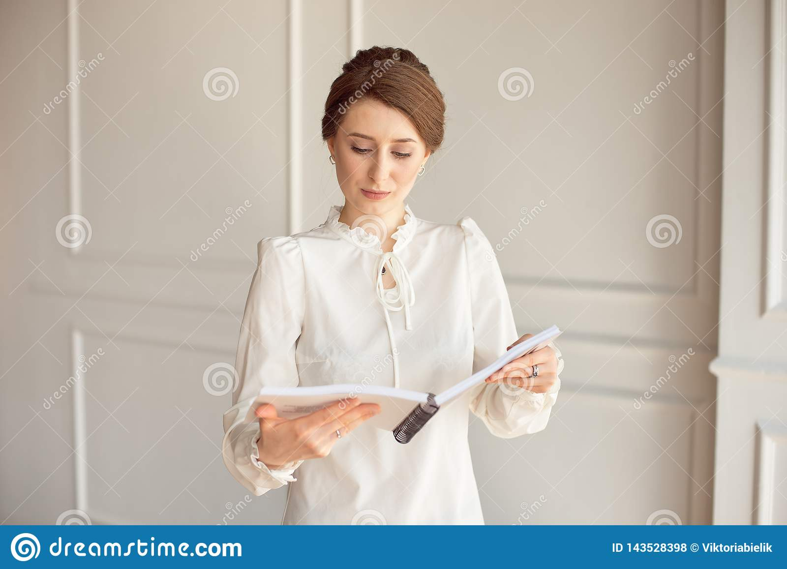 A mulher de negócio em uma camisa branca e em uma calças preta olha documentos nas mãos