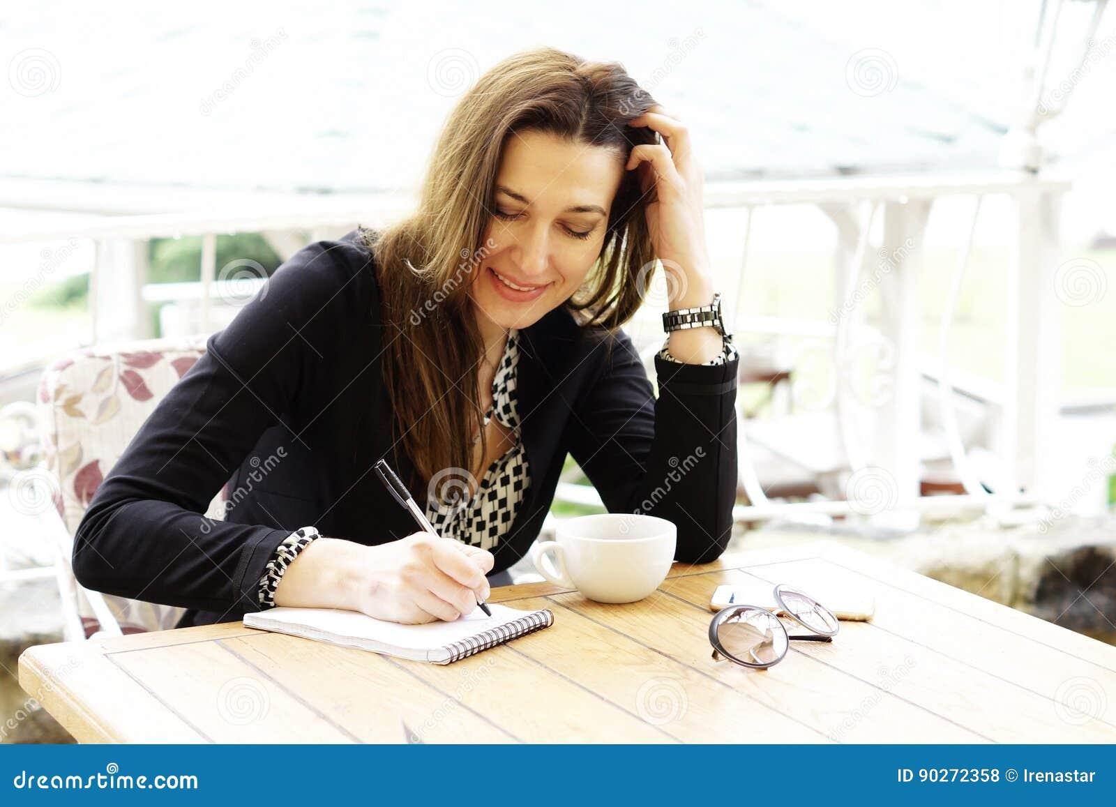 A mulher de negócio feliz de sorriso faz anotações em um caderno