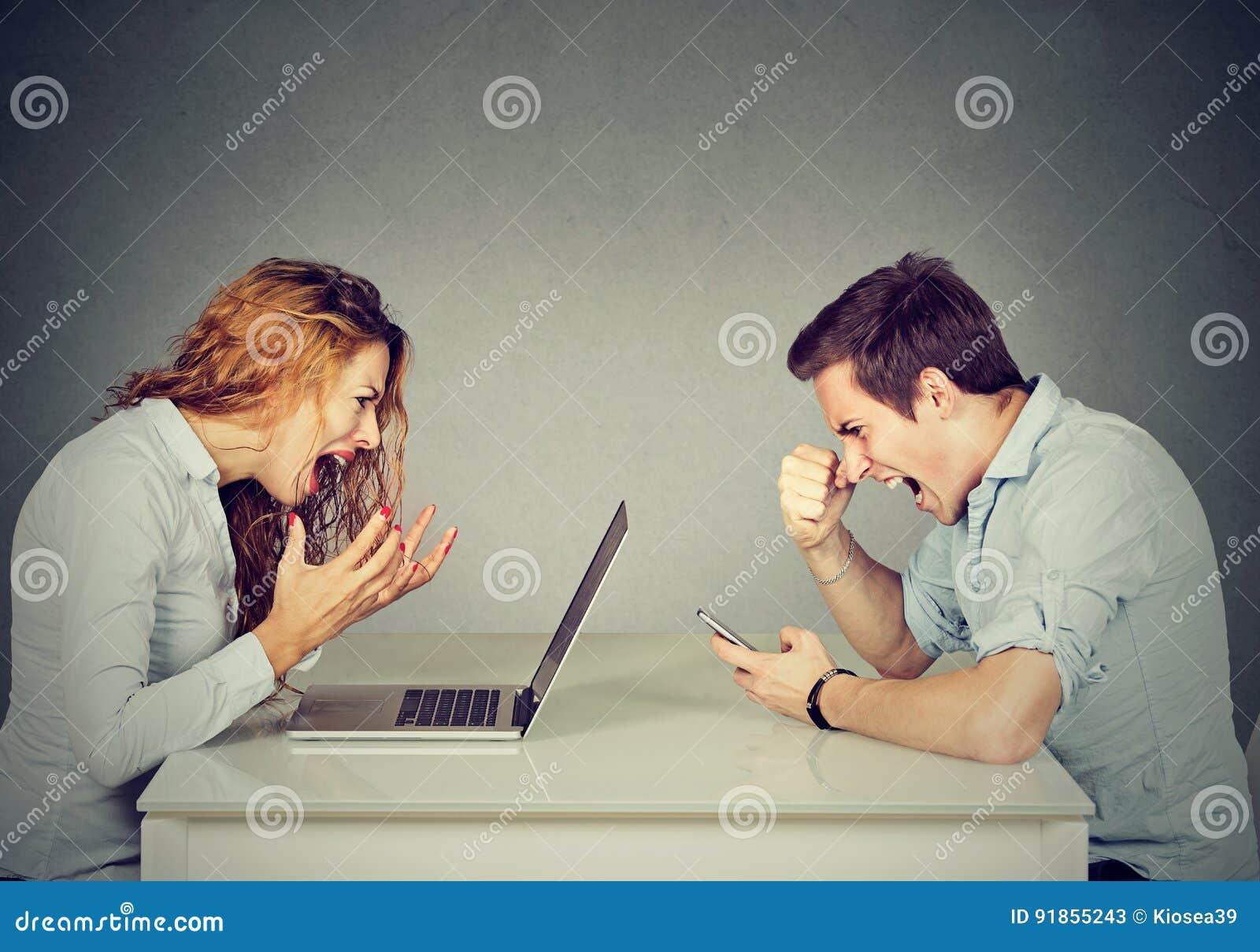 Mulher de negócio forçada com o portátil que senta-se na tabela com o homem irritado que grita no telefone celular Emoções negati