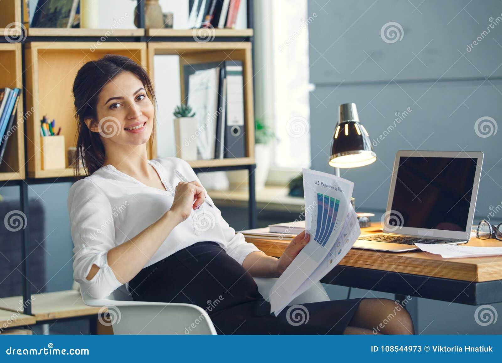 Mulher de negócio grávida que trabalha na maternidade do escritório que senta-se guardando o relatório do projeto