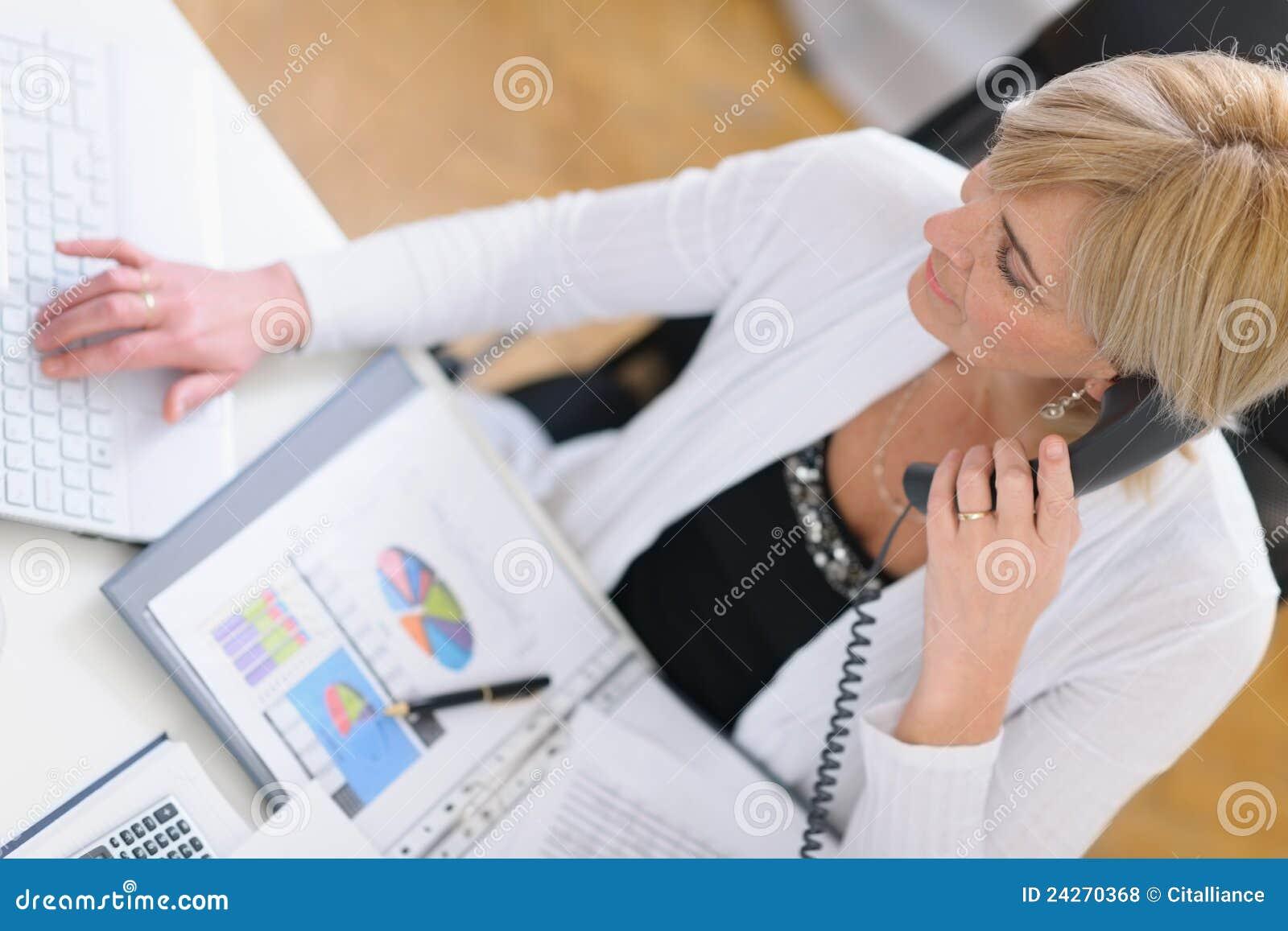 Mulher de negócio maduro que faz o atendimento de telefone. Vista superior