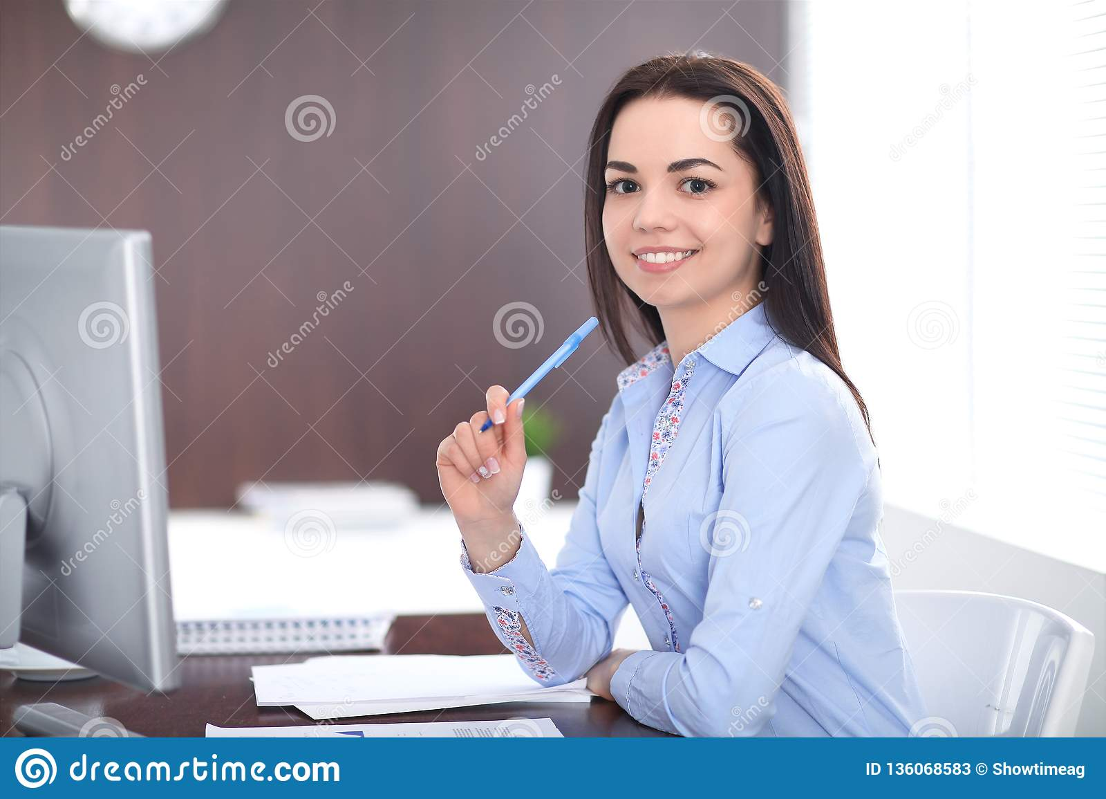 A mulher de negócio moreno nova olha como uma menina do estudante que trabalha no escritório Menina latino-americano ou latino-am